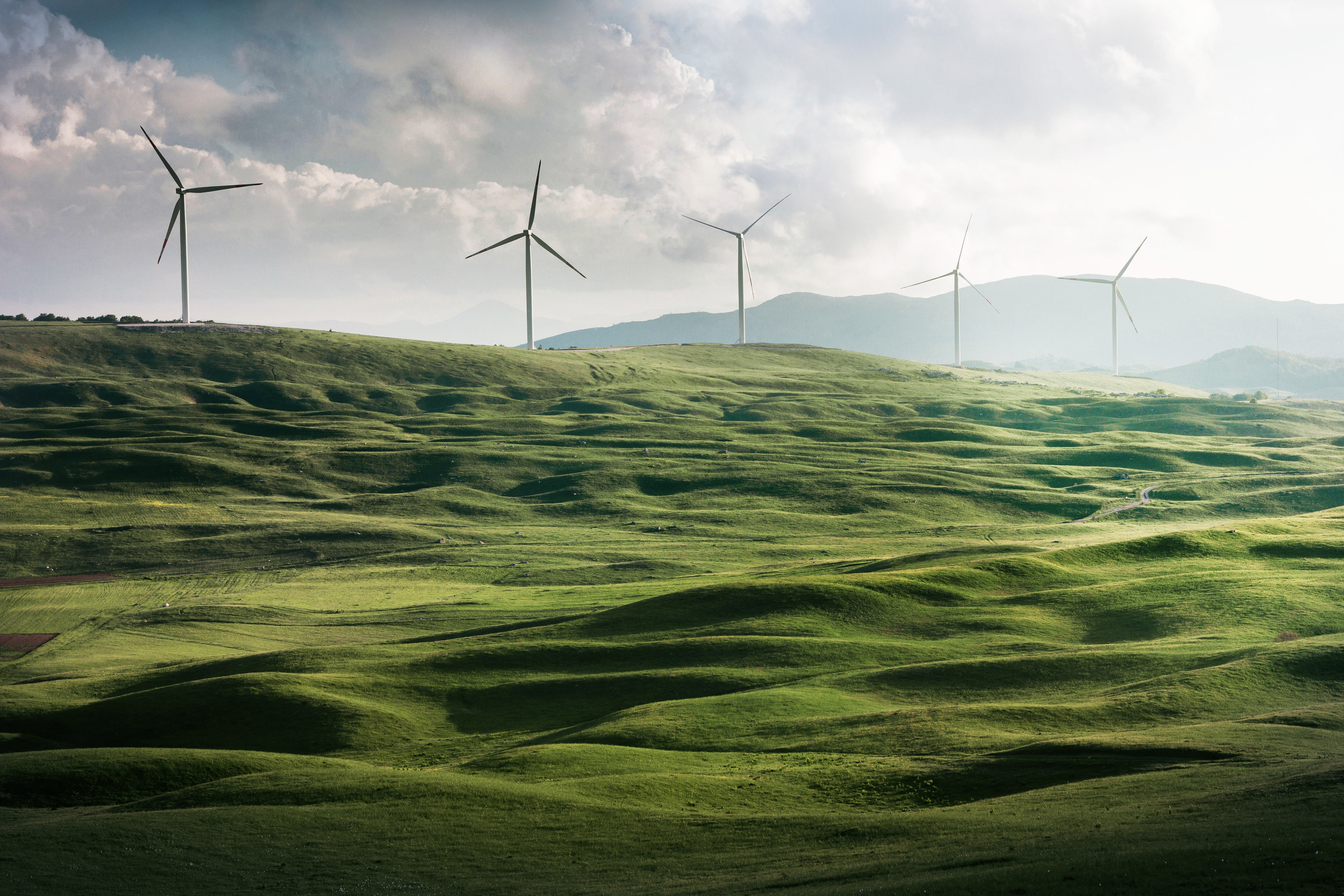 Windmills on a green hill providing green energy for the community